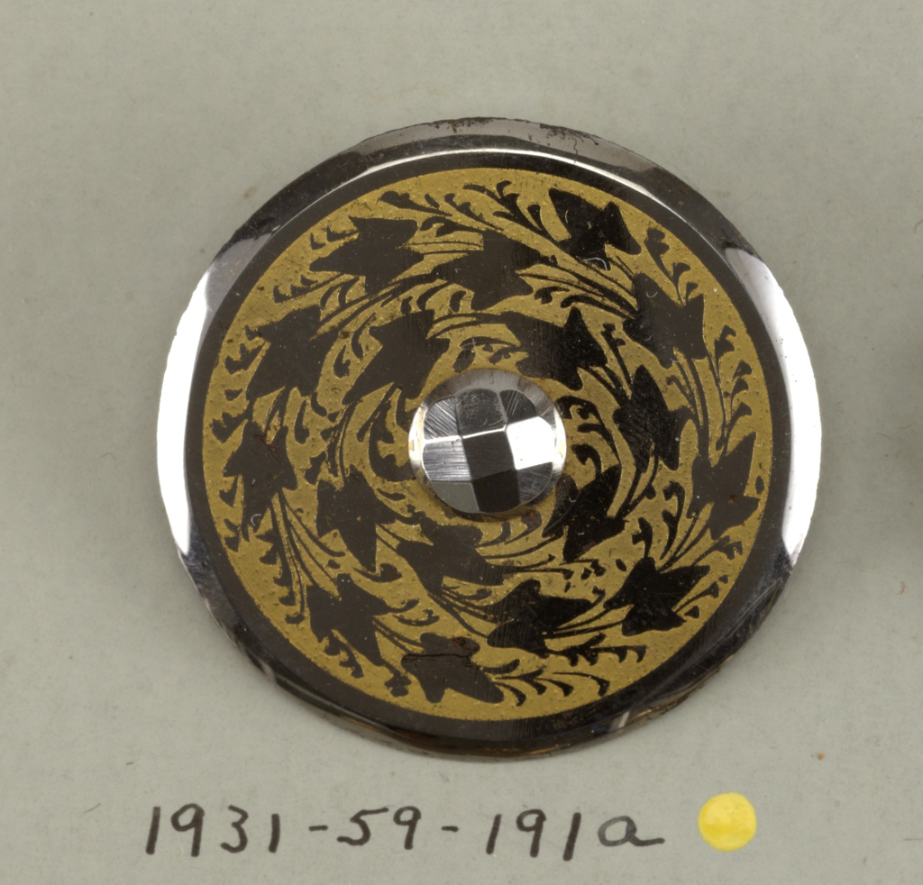 Flat, circular button with beveled edges; in the center, a facetted steel boss; surrounded by ivy leaves, in steel, against, a yellow ground.  On card 48