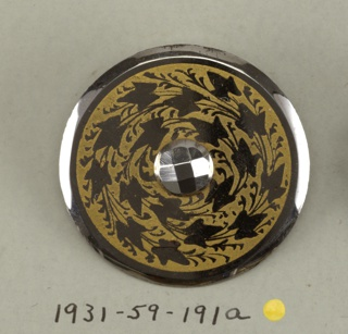 Flat, circular button with beveled edges; in the center, a facetted steel boss; surrounded by ivy leaves, in steel, against, a yellow ground.