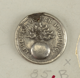 "Button with raised design of a flaming bomb surrounded by ""Liberte Ordre Publique"".  Button worn by grenadiers.  Component -b is on card H"