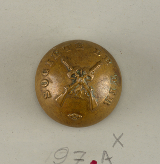 "circular button showing design of crossed rifles with the words ""Societe de tir""; on reverse ""A. M. et cie Paris 20 M"", brass shank.  Component -a is on card H"