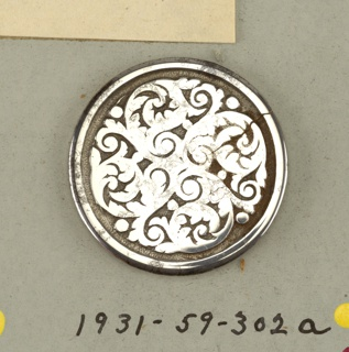 circular, flat button; ornamented with four swirled acanthus leaves - shank.