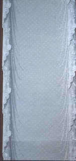 A panel of white drapery with lace trim along either edge. A red column runs the length between panels