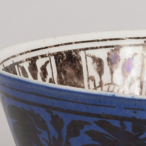 Deep bowl on small foot. Inside, a plant with five flowers in center, and single flowers between vertical bars on sides; outside, on medium blue ground, all-over pattern of flowers. All painting in lustre.