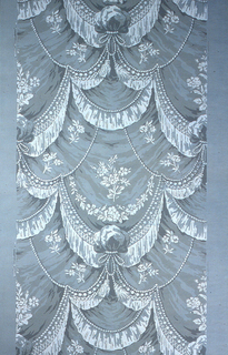 All-over pattern of drapery swags, with trims of rope twist, strung beads and tassels. A floral motif is printed on the drapery swags. Printed in gray and white on gray ground.