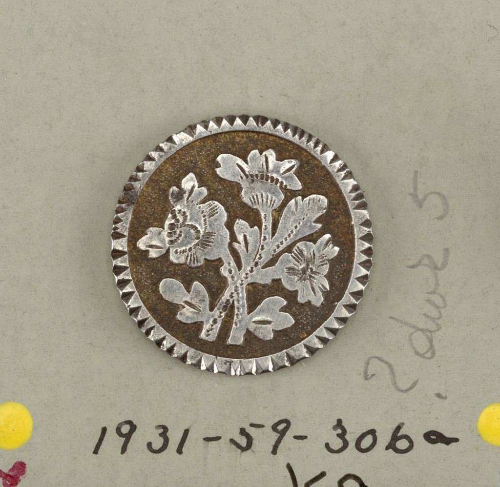 circular, flat button with ornament of crossed flower sprays in relief on yellow ground.