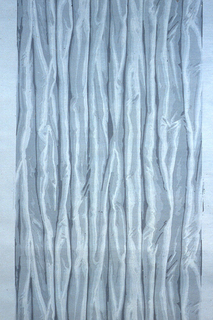 Drapery paper with the fabric hanging in soft pleats giving the effect of taffeta. Printed in shades of gray on gray ground.