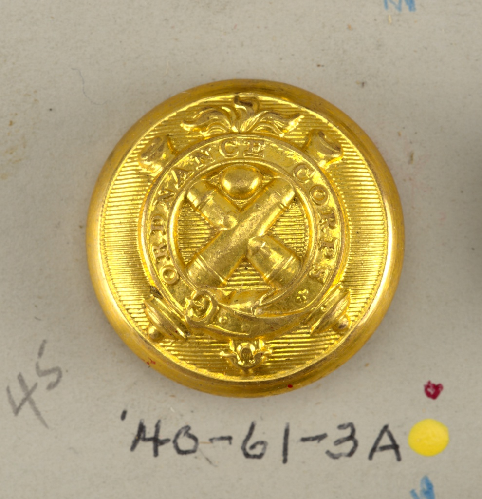 "one of an original set of 2 brass buttons with brass shanks [see: 1939-61-3-b for other button from the original set, which is deaccessioned.] - a/: this button is a reproduction of those used by officers in United States Army, Ordinance Corps 1840-47 - the button shows two crossed cannon with flaming bomb between and, on garter, ""Ordinance Corps"" - on underside, ""Scovill Mf'g Co. Waterbury"".