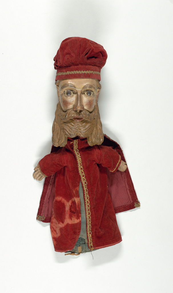 Head with wavy brown hair and beard. Red velvet cap with braid. Red velvet coat with cape, edged with braid, over green cotton sleeve. Painted wooden hands sewed into sleeves. Paint and gesso on face.