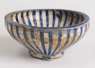Flaring bowl with incurvative rim.  Greenish-white glaze, running in heavy drops on outside.  Painted with radiating blue bands on inside and outside, and blue band on rim.  Some of the component parts iridescent.