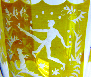 Thick circular foot, faceted edge and top, rising to swelling, faceted stem; bowl faceted, yellow stain cut away to reveal 3 rectangular panels decorated with figural scenes - - one with juggler and dog, one with woman holding birds, one with man in jester's hat - - each figure framed in stylized leafy vines.