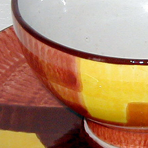Hemispherical cup (a) with roughly D-shaped tab handle on side, and short cylindrical foot.   Brushed underglaze decoration of light brown field with geometric panels in yellow, orange and dark brown; dark brown band at mouth; white interior. Circular saucer (b), with wide up-curved rim; brushed underglaze decoration of thick bands in browns, yellow, and orange on white ground.