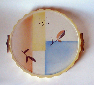 Circular, with zig-zag shaped edge, two projecting handles also zig-zag.  Top decorated with red, yellow and blue geometric shapes, two sprigs, a patch of dots, in browns and oranges.