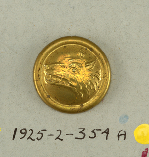 """Circular button with shank, backed with tin.  a: Ornamented with wolf's head within a band; Tin is ornamented with leaf design and letters """"IA"""" [?].  Component -a is on card 49"""