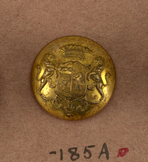 "Convex button with ornament showing heraldic devices on a shield, lion supporters, crown above and leaf ornament below. Back and shank of brass. On reverse, ""Superfins Paris E.B.""  On card i80"