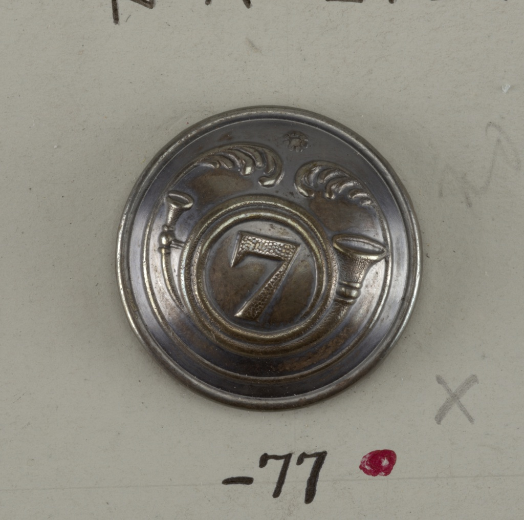 "Convex button ornamented with French horn placed around the number ""7"", and within a curve ending in leaf motifs. Brass back and shank. On reverse: ""Brunier Marechal Lyon"".