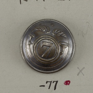 """Convex button ornamented with French horn placed around the number """"7"""", and within a curve ending in leaf motifs. Brass back and shank. On reverse: """"Brunier Marechal Lyon"""".  On card D"""