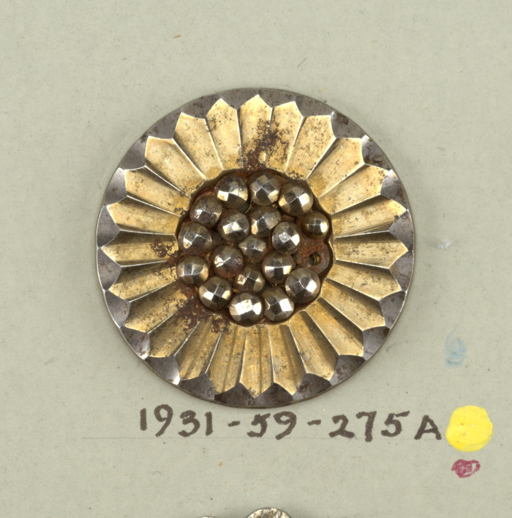 flat button in daisy design - group of knobs, center, surrounded by pointed petals - button has received a brass wash.  On card 58