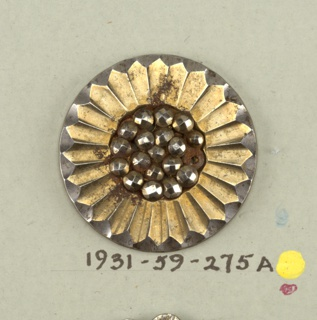 flat button in daisy design - group of knobs, center, surrounded by pointed petals - button has received a brass wash.