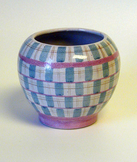 Squat ovoid body with circular foot.  White crackle ground decorated with pink horizontal bands alternating with rows of  blue rectangles and light brown hatched lines.