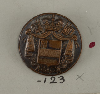 Flatt button ornamented with shield showing heraldic devices placed on mantle held by a crown at top; flags under mantle.