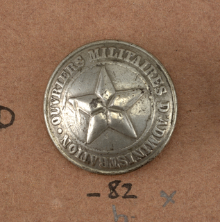 "Five-pointed star surrounded by the words ""Ouviers Militaires d'Administration"". In use during the years 1854-1858.  Component -b is on card i80 Component -c is on card J"