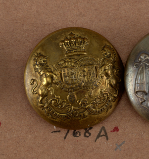 "Convex button showing coat of arms; two shields with heraldic devices surrounded by chains, lions supporters, crown above and below, ribbon with ""Porro unum est necessitarium"". Brass back and shank. On reverse, ""Firmin and Sons, 153 Strand London"".  On card i80"
