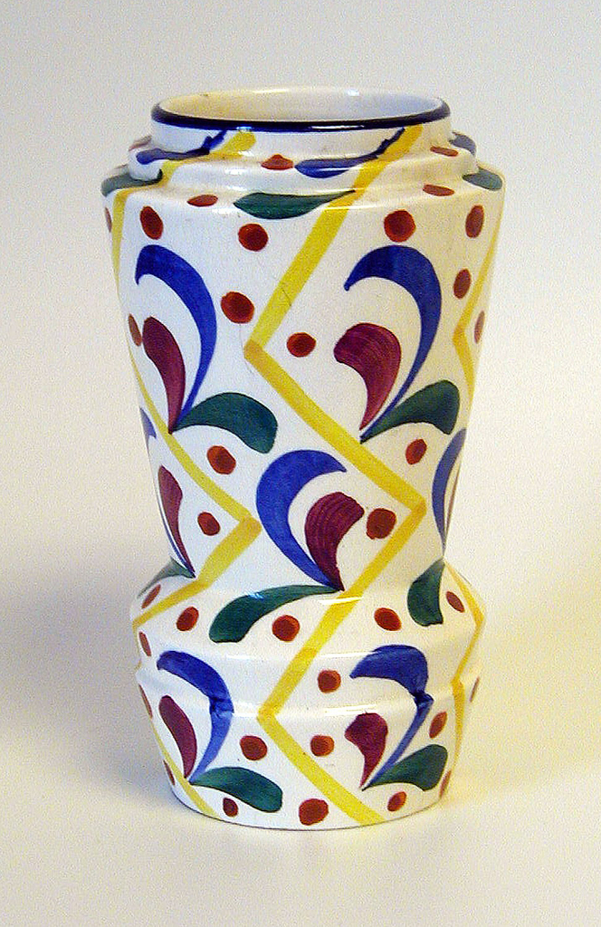 Tapering cylindrical body, stepped at neck and base; white ground decorated with red dots and sprigs of red, green and blue dispersed between yellow vertical zig-zag lines; black band at mouth.