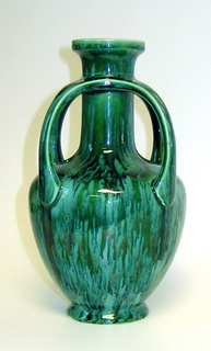 Inverse egg-shape body that tapers abruptly into a cylinder neck and flared mouth.  There are 4 curved handles that extend from below the mouth to the top of the body. It is all  glazed in bluish green.