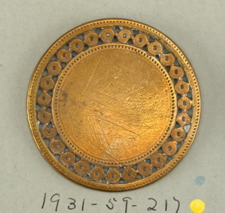 Flat circular button with band of pierced ornament on outside.