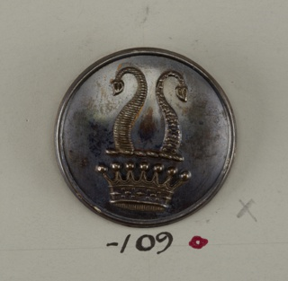 """Button ornamented with a crown and above that, two horns, one ringed and one speckled. On reverse, """"Ortner and Houle 3 St. James St. London"""".  On card D"""