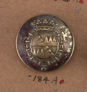 """Slightly convex button with heraldic devices, encircled by a chain and surmounted by a crown. Back and shank of brass. On reverse, """"Dagbert and Matheissen Place Beauvau.""""  Component -a is on card i80"""