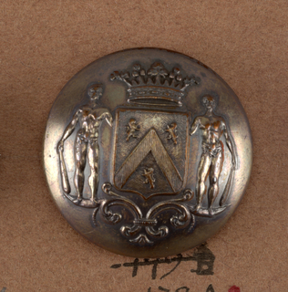 """Circular, convex button showing ornament of shield with heraldic devices, men supporters, leaf ornament below and crown above. Brass backs and shanks. On reverse: """"Moos Paris"""".  Component -a is on card i80 Component -b is on card C Component -c is on card E"""