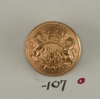 "Convex button ornamented with shield with heraldic devices; lion supporters resting on ribbon with ""Nihil sine deo"" on it; shield surmounted by crown. Brass back and shank. On reverse, ""Extra Fein"".