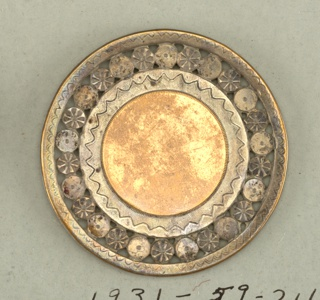 A) Copper center with pierced and engraved nickel border; B) Nickel plated button with copper band and gouging on nickel C) Nickel plated button with engraved cooper band D) Cooper button with stripes of horizontal and vertical line, set in copper rim.