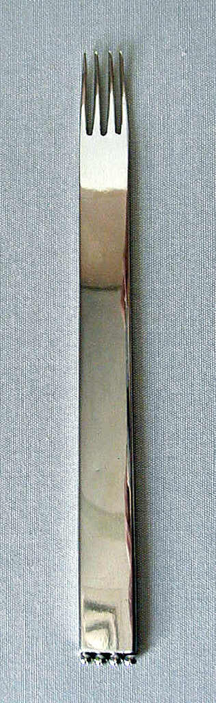 Flat, rectangular in form, handle tapering very slightly towards head; four tines, the head with very slight cupping shape; four hollow beads attached at bottom edge of handle.