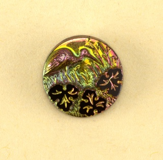 Iridescent button showing a bird, tall grass, and three leaves  On Cooper-Union exhibition card 8.2