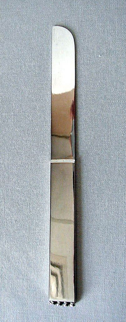 Flat, rectangular in form; handle tapers very slightly towards base of blade; blade straight with curved end; four hollow beads attached to bottom edge of handle.