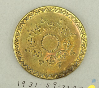 Two flat brass buttons ornamented with engraving: A) eight circle and maple leaves around central circle within border of zigzag lines and dots. B) central flower with rays within border of scallops and stars.