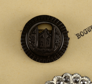 each of the five circular buttons is pierced in under side of rim with four holes for sewing, and ornamented on the top with design of Gothic Architecture.  These buttons belong to original set of thirteen buttons. for other objects originally in the group see: 1941-91-1-b,d, f/h, j, k, and m. which are deaccessioned.  Components a,c,e,l are on card 37 Component -i is on Cooper Union Exhibition card 4