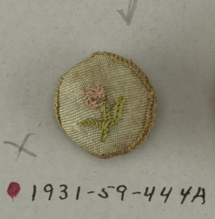 button made of wooden molds covered with green silk ornamented in design of flower with leaves worked in chain stitch.  On card A