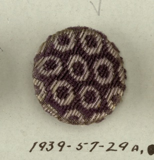 From originally a set of seventeen buttons, of three different sizes, to go with the man's suit of which 1939-57-30-a to c are parts - bone shapes covered with purple velvet uncut pile which forms minute hexagons each enclosing a round dot against a ground with short floats of secondary purple silk weft.  Component -a is on card A