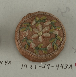 button made of wooden molds covered with pink silk ornamented with ribbon and silk sewing thread in design of an open flower within a wreath of leaves.  On card A
