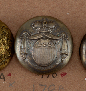"Convex button showing ornament of oval shield with three birds above perpendicular reed, with mantling (ermine?) and drapery held by a crown. On reverse:  ""Brevete Bruelles HA"". Brass back and shank.  On card i80"