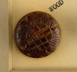 2 circular wooden buttons with wooden shank [originally from a set of 10 /see: 1939-59-1-c/k: deaccessioned] -  each 2 buttons ornamented with one four-petalled flower with raised center - see: 1939-59-1-c/k for the rest of the buttons [deaccessioned], which were originally a part of the set with these two.  Component -a on card 37 Component -b is on Cooper Union Exhibition card 4