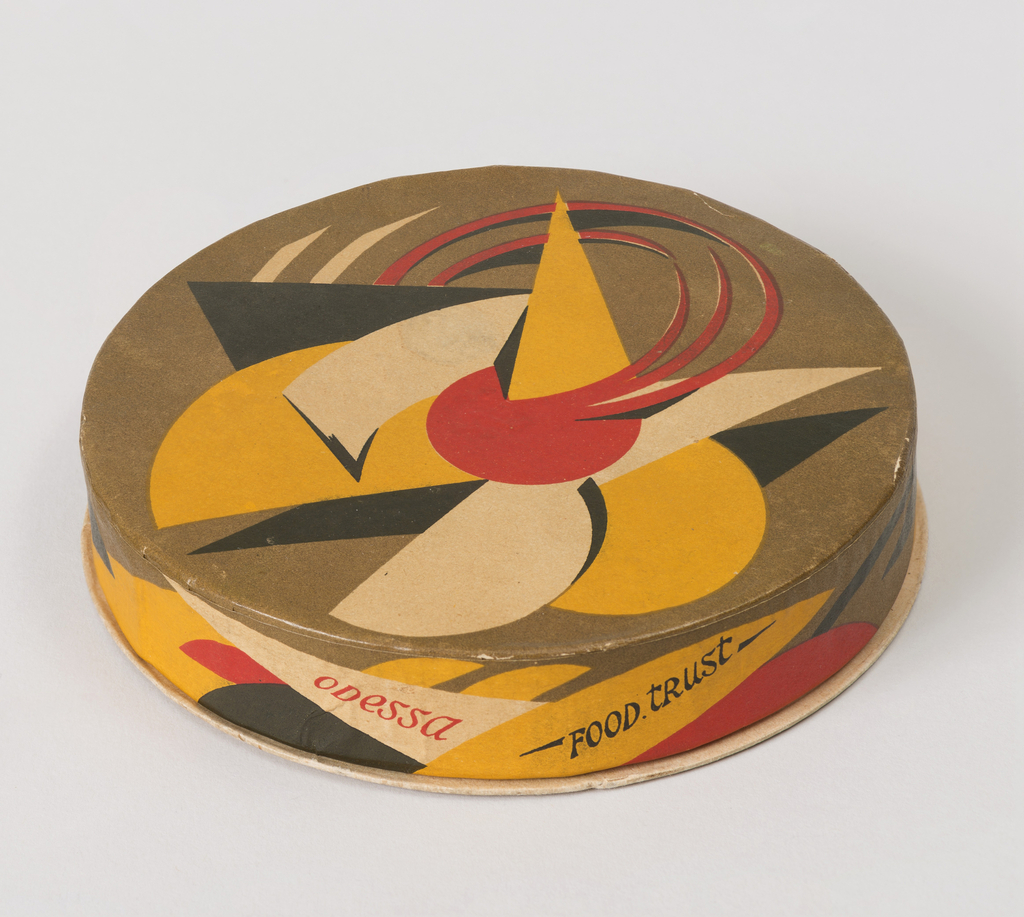 "Low, circular box and lid with printed abstract geometric decoration in olive green, yellow, red and black; the english words ""ODESSA (in red) / FOOD. TRUST (in black)"", ""net. 4 oz."", ""Made in U.S.S.R. (Russia)"" printed on the side of the lid."