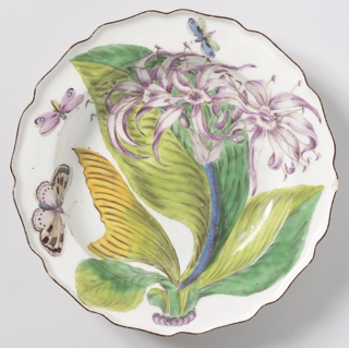 Deep well, marli with wavy rim, turned up. Decoration showing large, ribbed leaves, purple lily-type flowers and three butterflies. Brown line at rim.