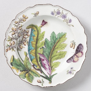 A plate with a wavy, brown-edged rim painted with a branch of bocconia/parrot weed (Bocconia frutescens) leaves, various sprigs, a caterpillar, and two winged insects.