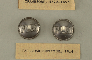 Convex buttons with rope edges and letters PLM; standing for Paris-Lyon-Mediterranee railway.  On card J