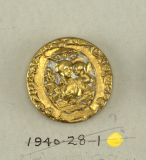 Circular button with metal shank. Stamped ornament showing seated woman with cupid enclosed in frame with floral ornament.