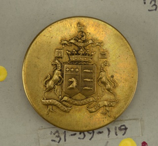 "Flat button ornamented with shield and banners showing heraldic devices held by horse supporters standing on a ribbon with ""Indomitum domuere cr--es""; surmounted by crest, ribbon with ""guerre"" and crown. Brass shank and back. On reverse: ""Superieur France""